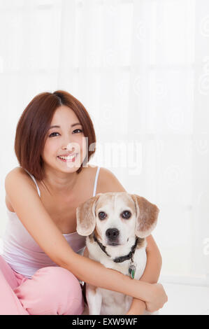 Young woman embracing dog and smiling at the camera, - Stock Image
