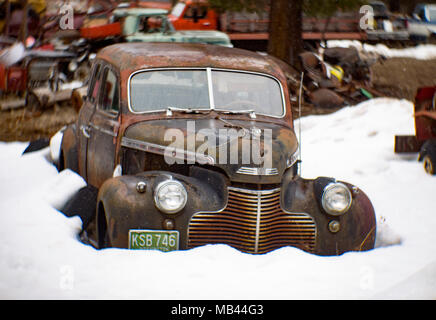A black 1940 Chevrolet Special Deluxe 4-door sedan, behind a barn, in Noxon, Montana  This image was shot with an antique Petzval lens and will show s - Stock Image