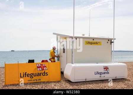 A lifeguard entering an RNLI lifeguard station - Stock Image