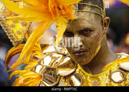 Dancers wearing golden costumes at the Battle of Flowers - Stock Image