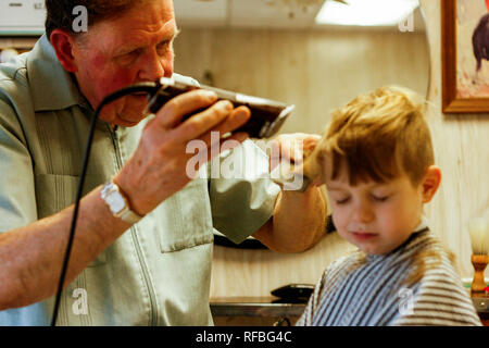 A barber cuts  young boy's hair in a Pennsylvania barbershop - Stock Image