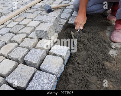 Construction worker making a pavement for renovating a street in an old city center - Stock Image