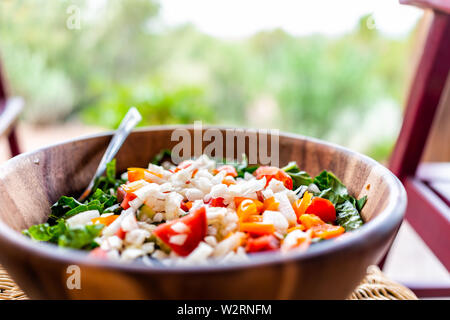 Closeup of fresh salad in wooden bowl with lettuce and bell peppers onions and bokeh background of rocking chair in garden patio - Stock Image