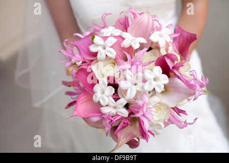 A bride clutching a bouquet of white roses and pink lilies. - Stock Image