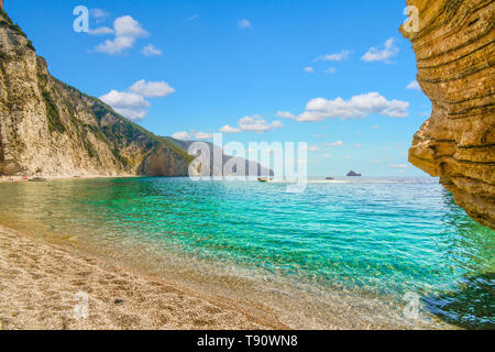 The turquoise aqua green clear water along the hidden cove of sandy Paradise Beach, also known as Chomi Beach in the Aegean Sea off Corfu, Greece. - Stock Image