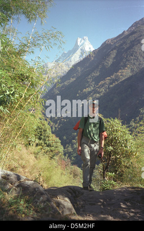 Trekker Mark Jones in bamboo forest with view of Machhapuchhre on Annapurna circuit Chomrong Nepal Himalayas - Stock Image