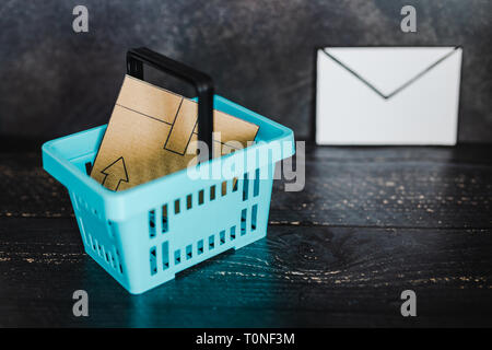 email marketing concept: shopping basket with parcel inside and email envelope next to it - Stock Image