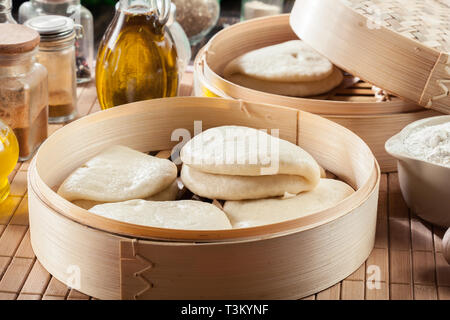 Gua bao, steamed buns in bamboo steamer. Asian cuisine - Stock Image