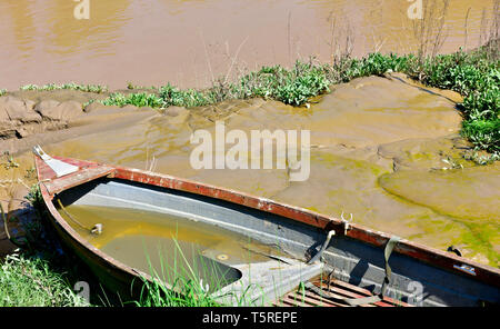 Small boat partly filled with water on mud bank of river - Stock Image