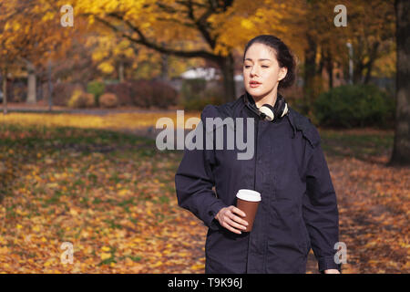 candid young hipster woman enjoying walk through park in autumn season holding coffee to go cup in her hand and headphones around her neck - Stock Image