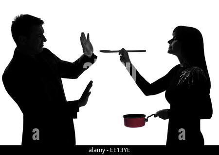 one caucasian couple man and woman tasting cooking sauce pan in studio silhouette isolated on white background - Stock Image