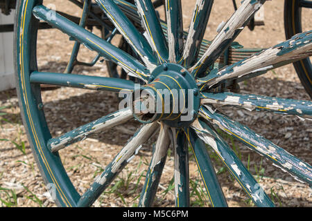 Close up of old buggy whell with green peeling paint - Stock Image