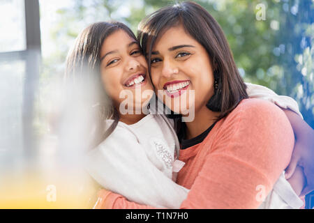 Portrait happy, confident, affectionate mother and daughter hugging - Stock Image