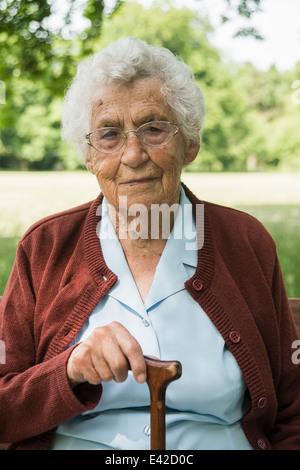 Portrait of senior woman, holding walking stick - Stock Image