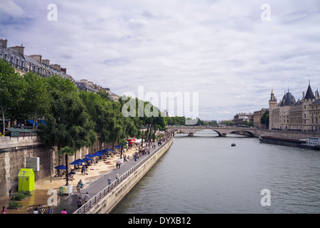 View of the Seine River, one of the artificial beaches and a bridge in the city of Paris, France. - Stock Image