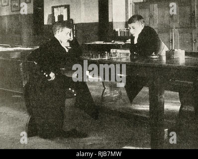 Two boys of the Bluecoat School (Christ's Hospital), founded by King Edward VI, originally in Newgate Street, City of London, but now in Horsham, West Sussex. Seen here playing a game of chess, wearing their distinctive uniform. - Stock Image