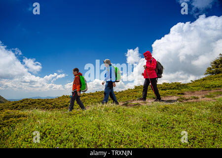 Mom with sons travel in mountains, family enjoy hiking - Stock Image