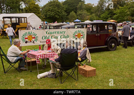 Vintage car enthusiasts taking refreshments alongside their vehicles at car rally. - Stock Image