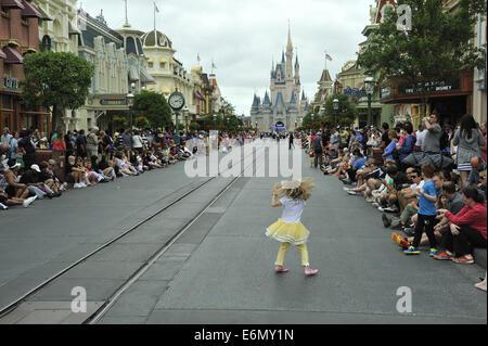 A little girl dances on the street awaiting Festival of Fantasy Parade. Magic Kingdom Park, Walt Disney World, Florida - Stock Image