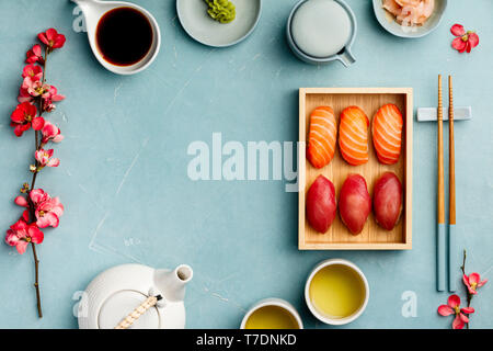 Nigiri sushi with salmon and tuna served on bamboo plate  with chopsticks, soy sause, wasabi, ginger and tea on blue background. Delicious traditional - Stock Image