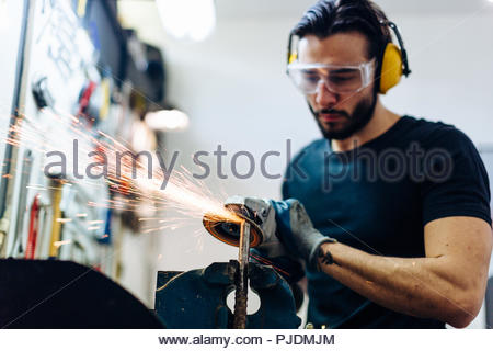 Young man using angle grinder on metal in workshop - Stock Image