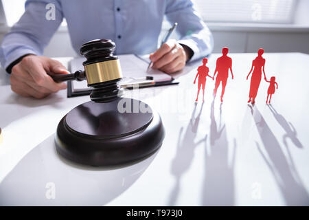 Close-up of mallet showing separation of family on desk - Stock Image