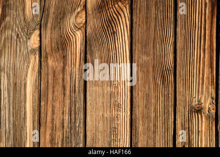 Aged wood texture with grain patterns due to the weathering effect of rain and harsh weather. Brown horizontal composition - Stock Image