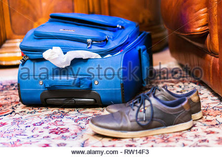 Rotterdam, The Netherlands - February 18, 2019: Blue opened travel suitcase laying on a carpet floor in a hotel room. Pair of brown leather shoes in s - Stock Image