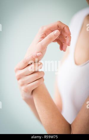 Woman suffering from an articular pain in the hand. - Stock Image