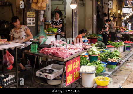 Street sellers selling exposed meat and vegetables on a food stall at roadside in old quarter of Hanoi, Vietnam, Asia - Stock Image