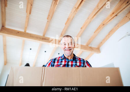A low-angle portrait of senior man furnishing new house, a new home concept. - Stock Image