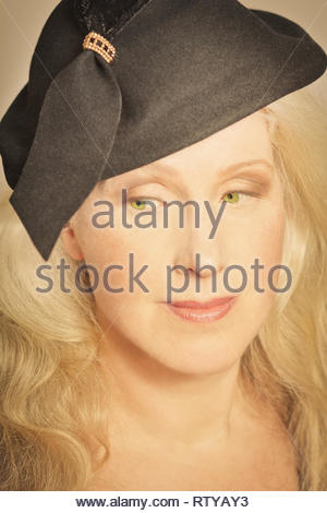 Closeup portrait of beautiful mature woman with long hair and vintage hat, faded retro filter effect. - Stock Image