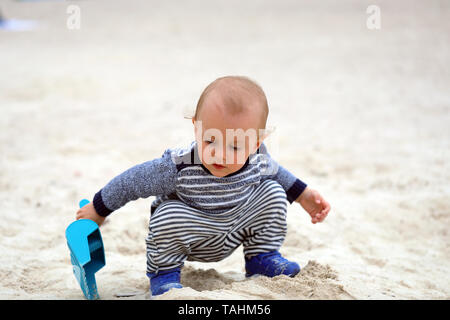 Cute Baby Boy Is Playing With Sand And Plastic Shovel On The Beach - Stock Image