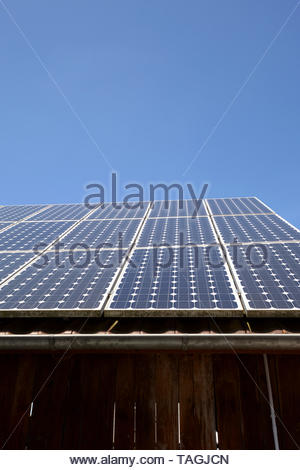 modern solar cells or photovoltaic on the roof of an old woodshed with new gutter in front of azure sky, solar panel on blue sky background - Stock Image