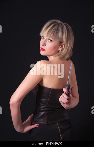 A blond model with large knife behind her back - Stock Image