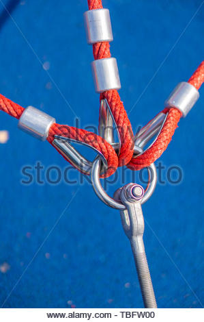 Three red ropes attached to a metal ring.  - Stock Image
