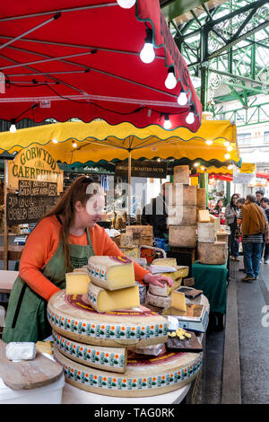 Borough Market Cheese stalls with red and yellow umbrella lit parasols display, with 'try before you buy' tasting samples at Borough Market Southwark London SE1 - Stock Image