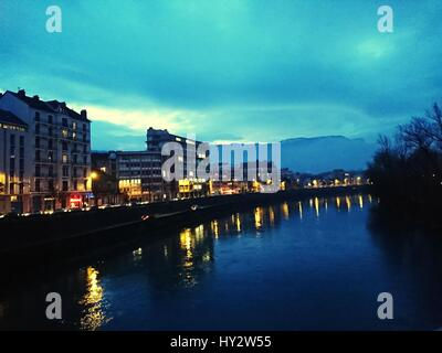 Illuminated Bridge Over River In City At Dusk - Stock Image