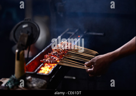 Cooking chicken satays at Ubud Markets Bali Indonesia - Stock Image