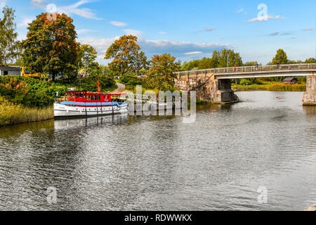 A boat docks along the banks of the Porvoonjoki river as visitors cross the bridge connecting to the medieval village of Porvoo, Finland. - Stock Image