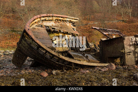 An old decaying fishing boat from yesteryear lies on the shoreline at Diabaig, Torridon in the Scottish Highlands - Stock Image