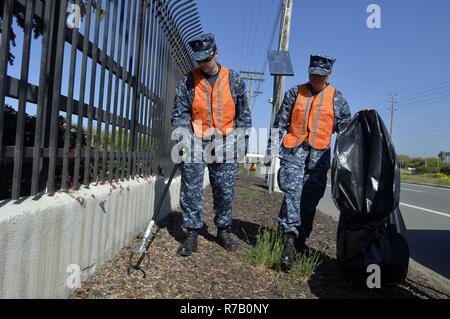 SAN DIEGO (April 12, 2017) Master-at-Arms 2nd Class Jessica Fendzlau and Master-at-Arms 3rd Class Mayra Sanchez, both assigned to Naval Base San Diego, pick up trash during base cleanup. The all-hands event is hosted by Naval Base San Diego First Class Petty Officer Association in an effort to clean and improve the appearance of the naval base and promote morale. - Stock Image