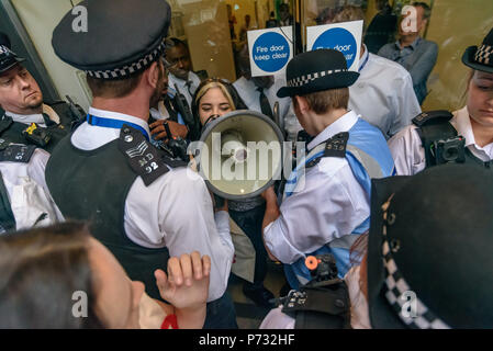 London, UK. 3rd July 2018.  More police surround the student who is holding the door of Southwark Council Offices open.  The protesters were calling on the Council Planning Committee to reject the plans by tax avoiding property giant Delancey and University of the Arts London to demolish the Elephant & Castle Shopping Centre  and replace it with luxury housing and a new building for the London College of Communication. Credit: Peter Marshall/Alamy Live News - Stock Image