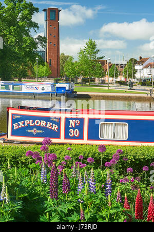 Canal boats in Bancroft Basin in Stratford upon Avon with the tower for the Royal Shakespeare Theatre in the background - Stock Image