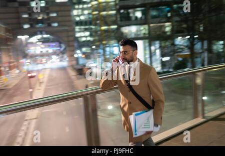Businessman talking on smart phone, walking on urban pedestrian bridge at night - Stock Image