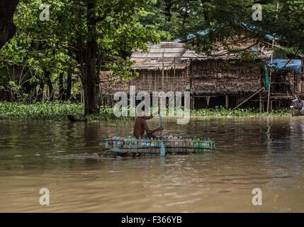 A boy paddles a boat made of recycled plastic bottles in a flooded village in the Irrawaddy delta, Myanmar. - Stock Image