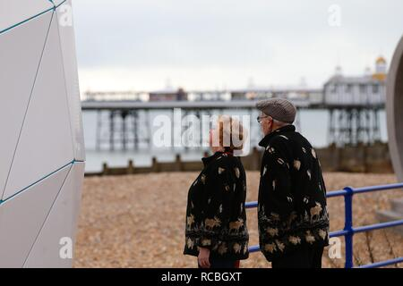 Eastbourne, East Sussex, UK. 15 Jan, 2019. UK Weather: A bright but chilly mid morning in Eastbourne on the seafront promenade with people jogging and taking a walk enjoying the dry weather.  This couple admire the iconic beach huts. © Paul Lawrenson 2018, Photo Credit: Paul Lawrenson / Alamy Live News - Stock Image