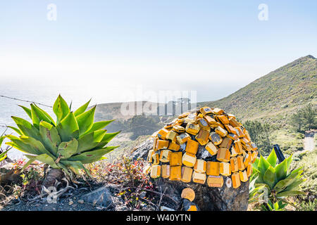 A creative sculpture made up of orange and yellow reflective highway markers located on the side of highway 1 in California's Central Coast near Big S - Stock Image