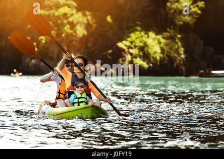 Happy family of three kayaking in sea bay at tropical islands background - Stock Image