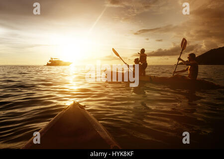 Two kayaks with family at sunset sea - Stock Image